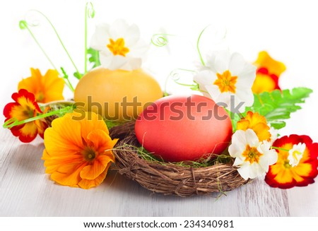 Easter egg in nest with spring flowers - stock photo