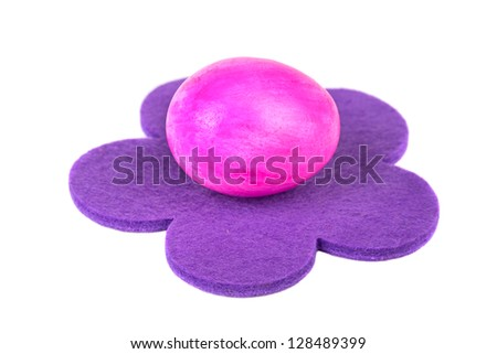 Easter egg on the violet flower, on a white background