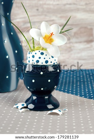 Easter egg vase with open white crocus flower on neutral background - stock photo
