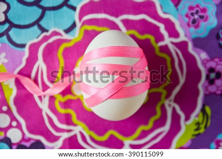 Easter egg wrapped in pink satin ribbon on a beautiful, bright, colorful abstract background, Easter egg on colored background - stock photo