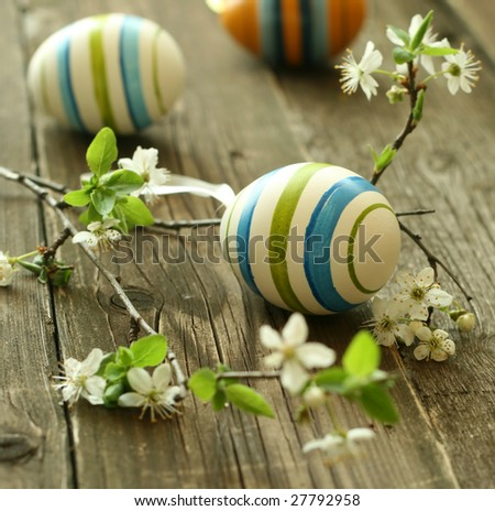 Easter eggs and branch with flowers on wooden - stock photo