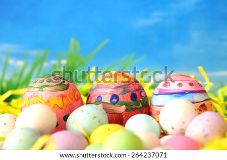 Easter eggs and candies in on nest with blue sky (eggs decorated by kids)