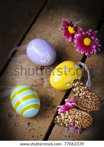 Easter eggs and daisies, and butterfly on old vintage table top with copy space - stock photo