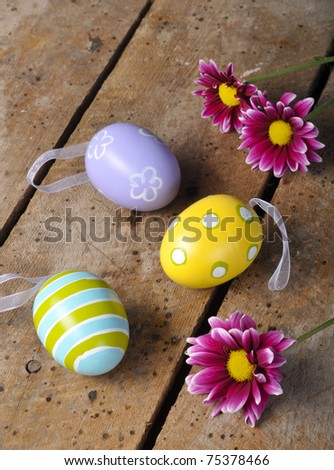 Easter eggs and daisies on old vintage table top with copy space - stock photo