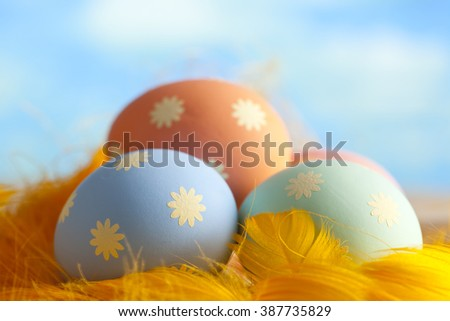 Easter eggs and feathers on sky background - stock photo