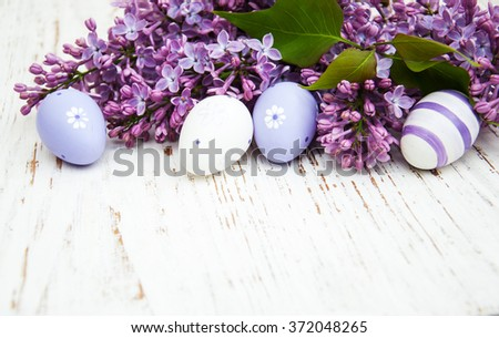 easter eggs and fresh lilac flowers on a old wooden background - stock photo