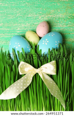 Easter eggs and grass on wooden background - stock photo