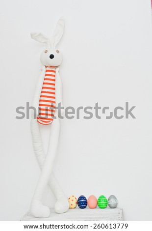 Easter eggs and handmade rabbit on white background - stock photo