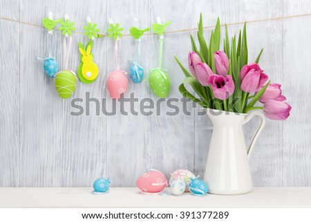 Easter eggs and pink tulips bouquet on shelf in front of wooden wall. View with copy space - stock photo