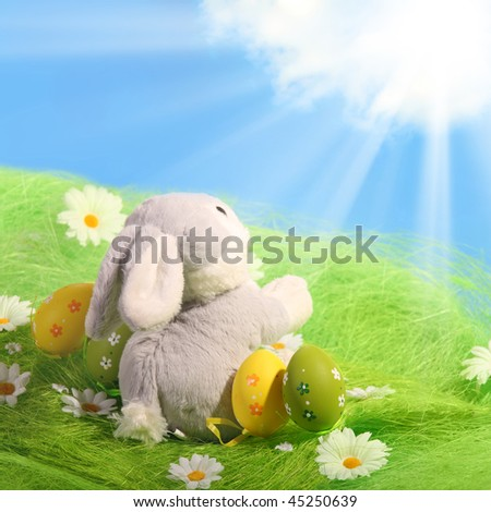 Easter Eggs and rabbit sitting on grass field with blue sky background