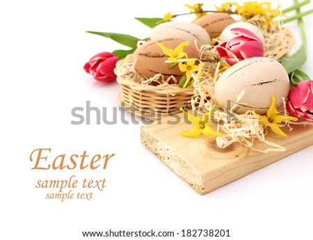 easter eggs and spring flowers on white - stock photo