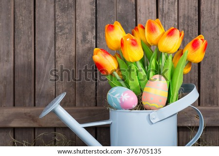 Easter eggs and tulips in a water can with a wood background