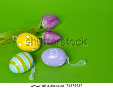 Easter eggs and tulips on green background with copy space - stock photo