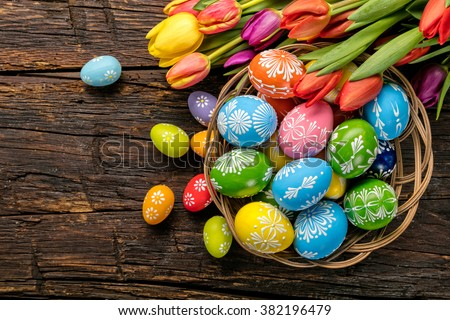 Easter eggs and tulips on wooden planks - stock photo