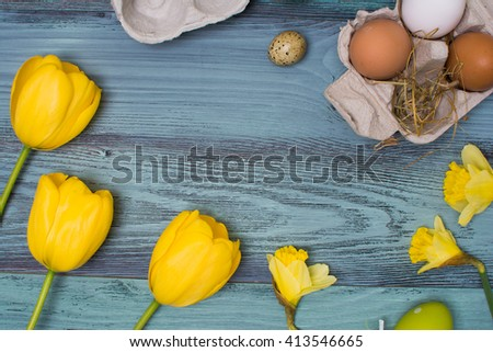 Easter eggs and tulips over blue wooden table. Top view.