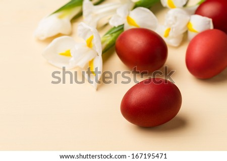 Easter eggs and white flowers on the beige table - stock photo