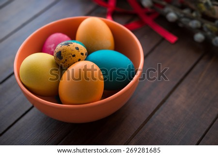 Easter eggs and willow tree on white wood table - stock photo