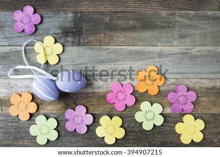 Easter Eggs and wooden flowers on wooden table with copy space. - stock photo