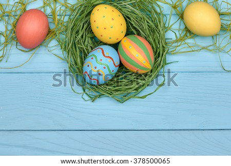 Easter eggs background. Hand painted multicolored decorated eggs on green straw nest, blue wood, copyspace. Unusual creative holiday greeting card  - stock photo