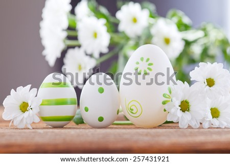 easter eggs between white flowers - stock photo