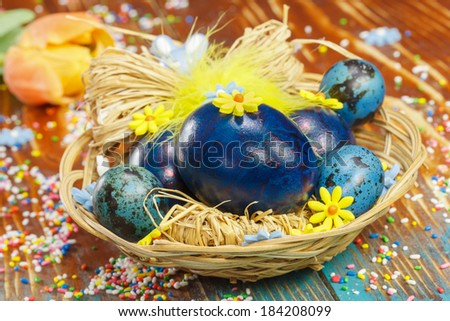 Easter eggs. Boiled Easter eggs in basket on wooden rustic table with tulip and colorful crumbs. Macro, selective focus - stock photo