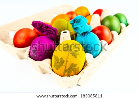 Easter eggs colored in traditional way labeled with natural leave sticker in carton egg box isolated on white - stock photo