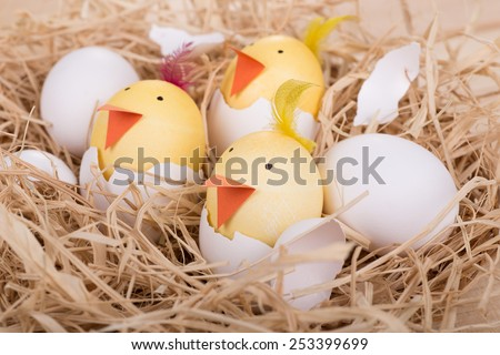 Easter eggs decorated as chicks hatching in a nest - stock photo
