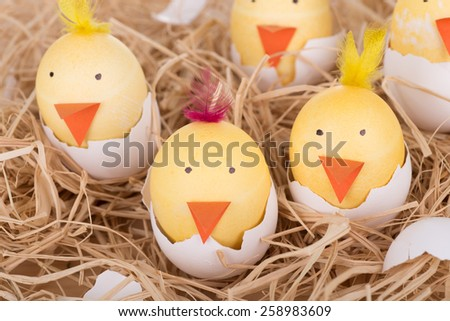 Easter eggs decorated as chicks hatching in a nest