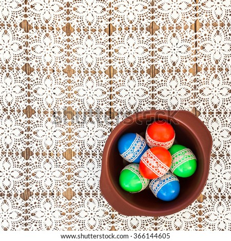 Easter eggs decorated with lace in a bowl  on white crochet tablecloth. Top view - stock photo