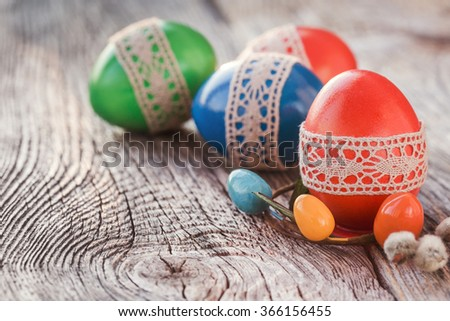 Easter eggs decorated with lace on wooden table. Selective focus, toned, soft focus - stock photo