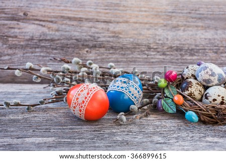Easter eggs decorated with lace, pussy-willow  and quail eggs in small nest on wooden background.  - stock photo