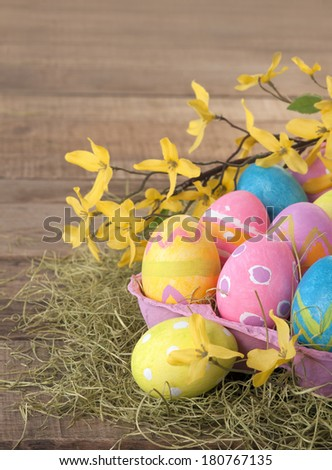 Easter Eggs Dyed by Kids in Rustic Still Life with Colorful Spring Forsythia Flowers in Bokeh, with background room or space for copy, text, words.  Vertical - stock photo