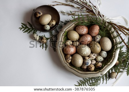 Easter eggs dyed with natural dyes in vintage bowl with willow twig, top view - stock photo