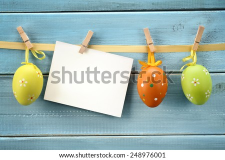 Easter eggs hanging on wood background with blank card. - stock photo