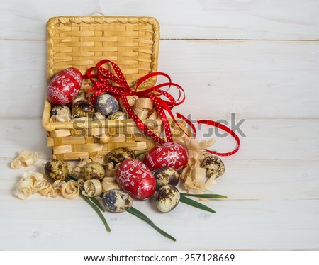 Easter eggs in a basket decorated with a red bow on a wooden background. Eve of Easter. - stock photo