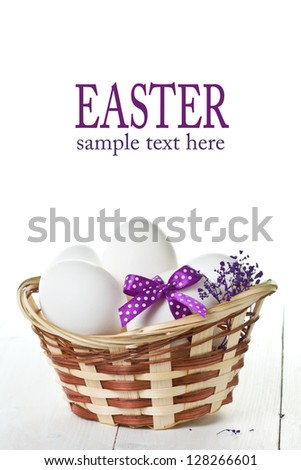 Easter eggs in a basket on white wooden table - stock photo
