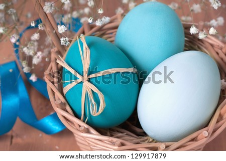 Easter eggs in a basket on wooden background - stock photo