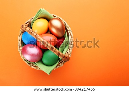 Easter eggs in a basket, top view - stock photo