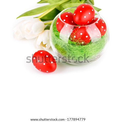 Easter eggs in a bowl with white tulips isolated on white - stock photo