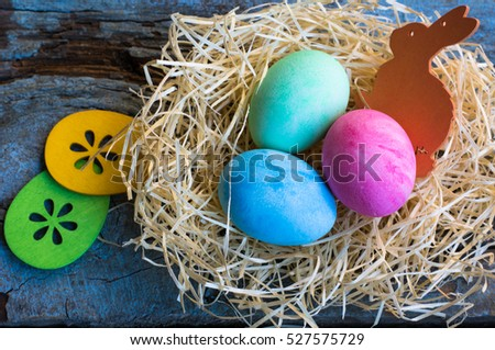 Easter eggs in a nest on rustic background