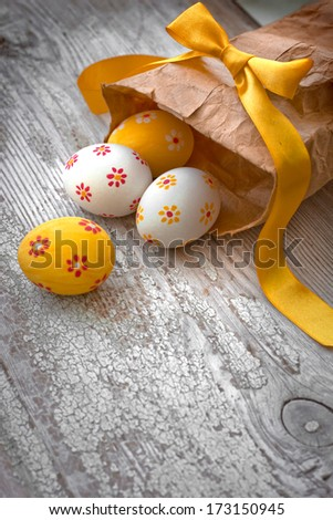 easter eggs in a paper holiday bag/ Easter eggs on wooden background - stock photo