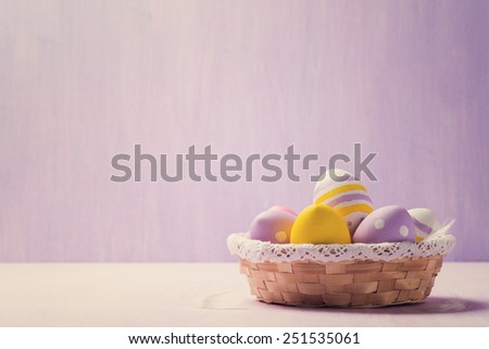 Easter eggs in a wicker basket. Space for text - stock photo
