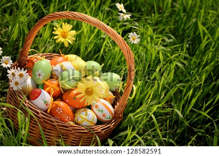 Easter eggs in basket on meadow - stock photo