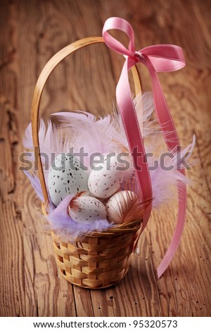 Easter eggs in basket on wooden background