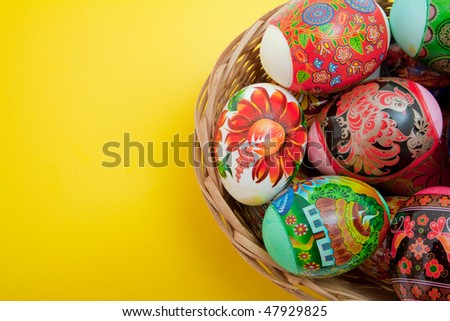 easter eggs in basket on yellow background - stock photo