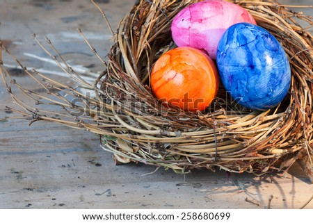 Easter eggs in basket, outdoor shoot, on rustic wooden table with grunge effects