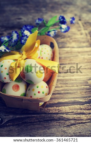 easter eggs in basket with bow on wooden background - stock photo