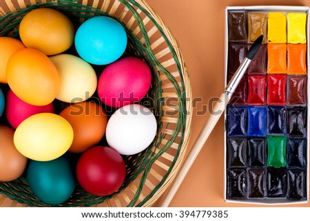 Easter Eggs in basket with paints and brush. Preparing for Easter. Top view - stock photo