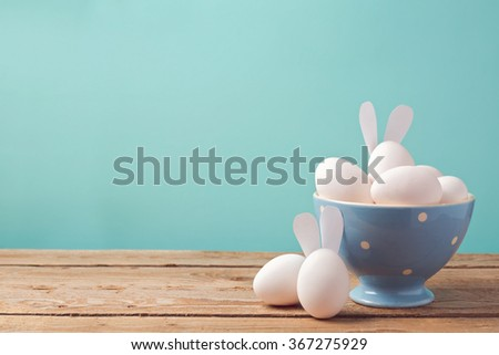 Easter eggs in bowl on wooden table with copy space - stock photo