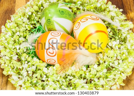 Easter Eggs in feather nest with Wreath Around on wooden background - stock photo